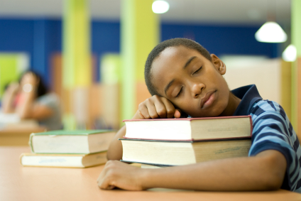 Child napping on stack of books.
